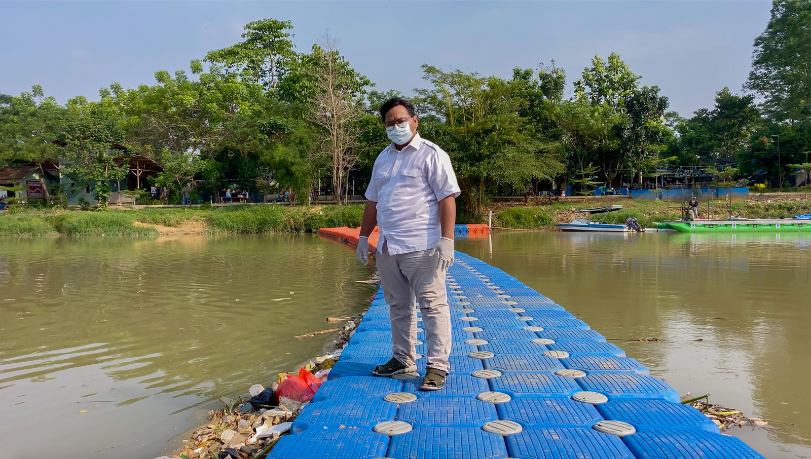 Ade Yunus, founder of environmental organisation Bank Sampah Sungai Cisadane (Cisadane River Waste Bank) or Banksasuci, stands on a floating boom used to collect waste from the Cisadane River in Tangerang, Indonesia.