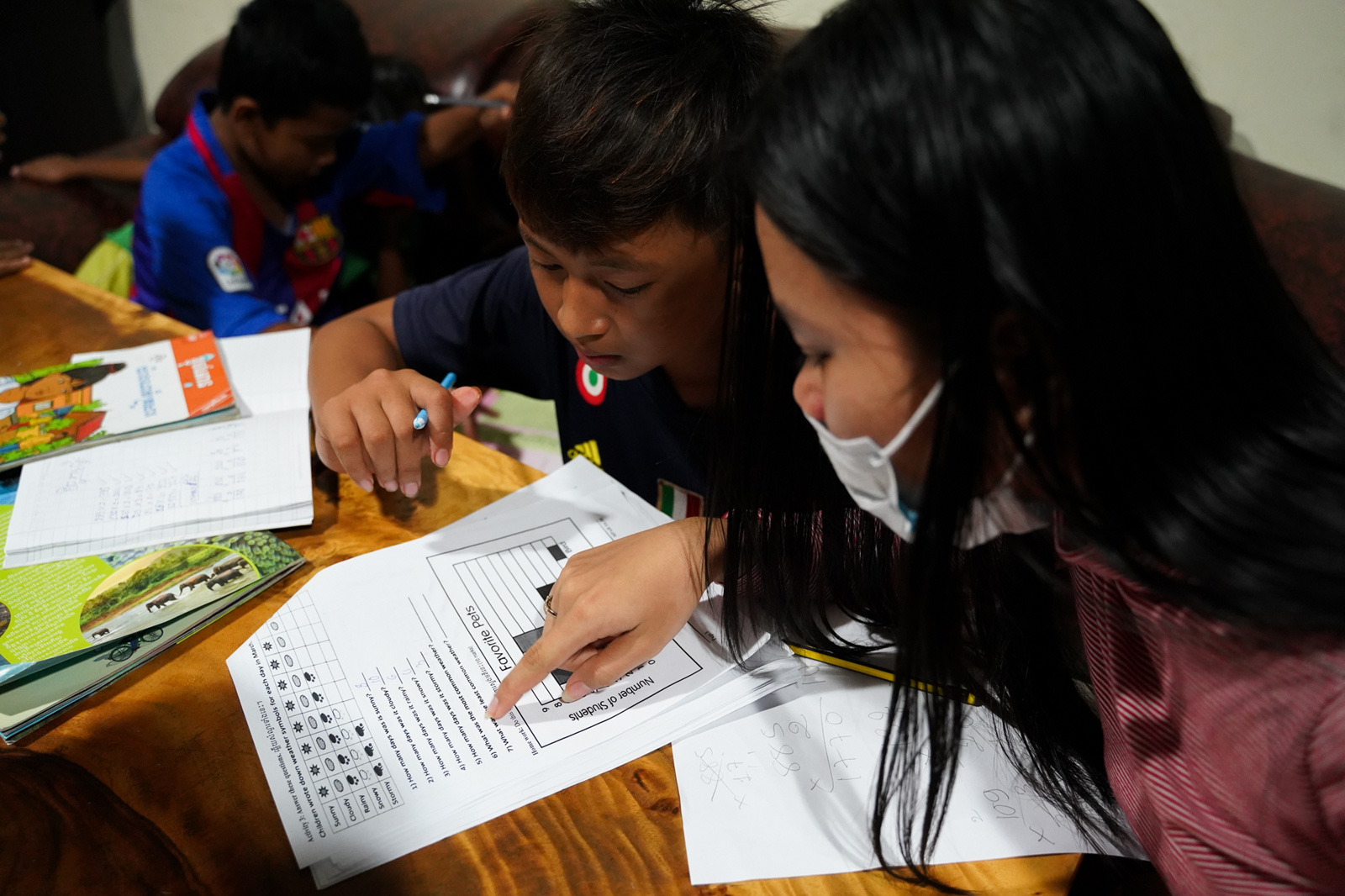 A student teacher helps a younger student with a worksheet from school.