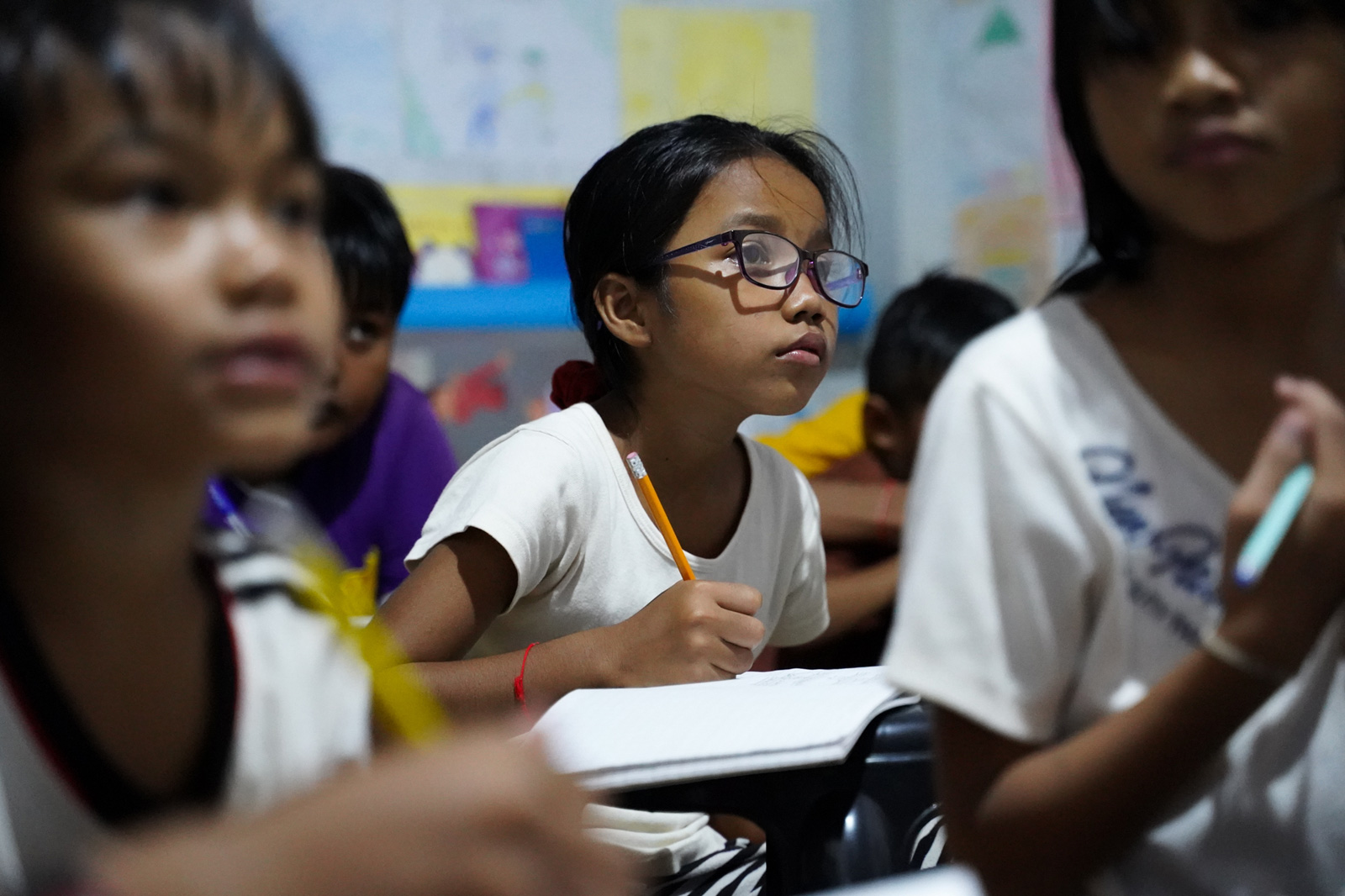 A young girl studies English at the Village Library in Nokor Thom Commune's Roha Village. The classes are free of charge and taught by young volunteers in the community.