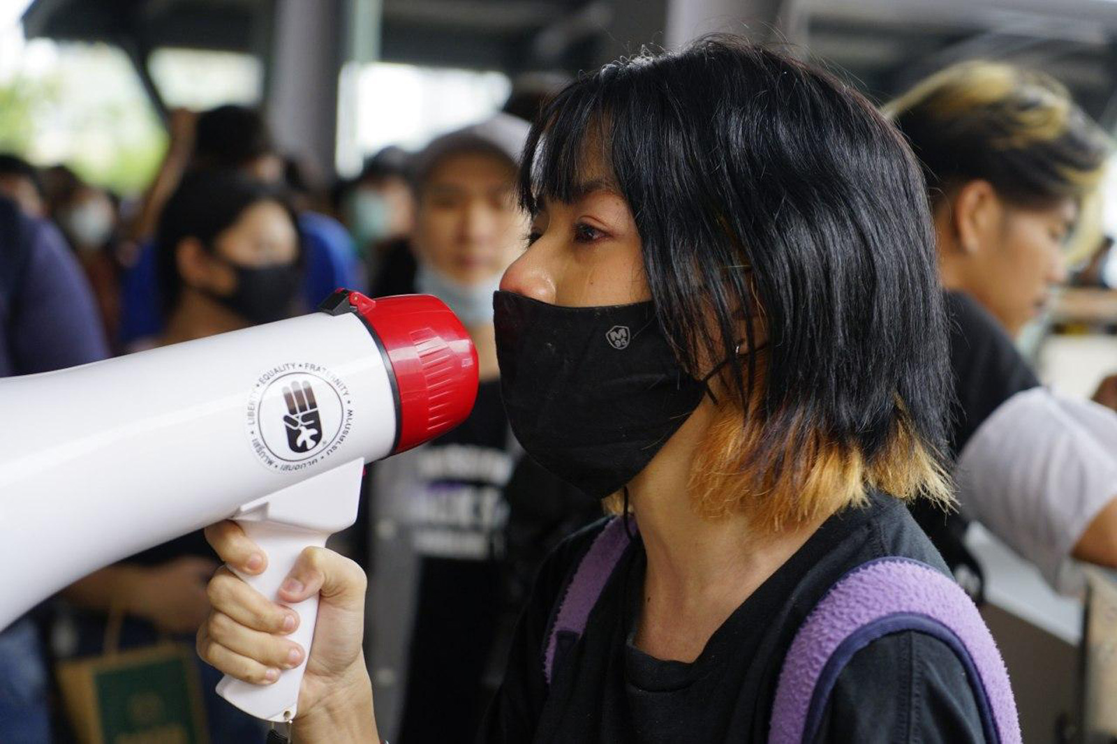 A protestor uses a megaphone during a flash mob at Lad Phrao intersection in Bangkok on 17 October 2020.