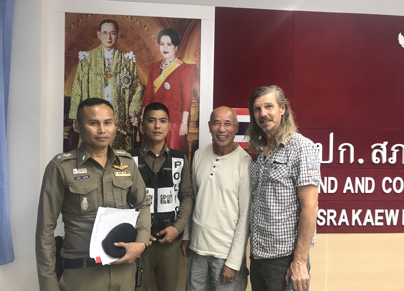 Cambodian-American CNRP supporter Hay Kimsan (second right) and American Daniel Capka pose with Thai police officers at Sa Kaeo police station on 8 November 2019.
