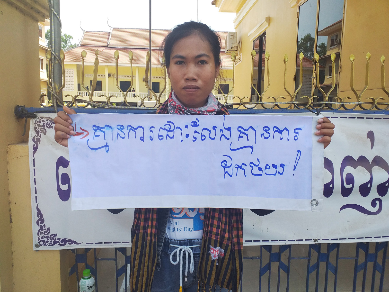 "Mother Nature Cambodia activist Long Kunthea protests the arrest of environmental activist Ouch Leng in Stung Treng province in March 2020, holding a sign reading: ""No release, no withdrawal."""
