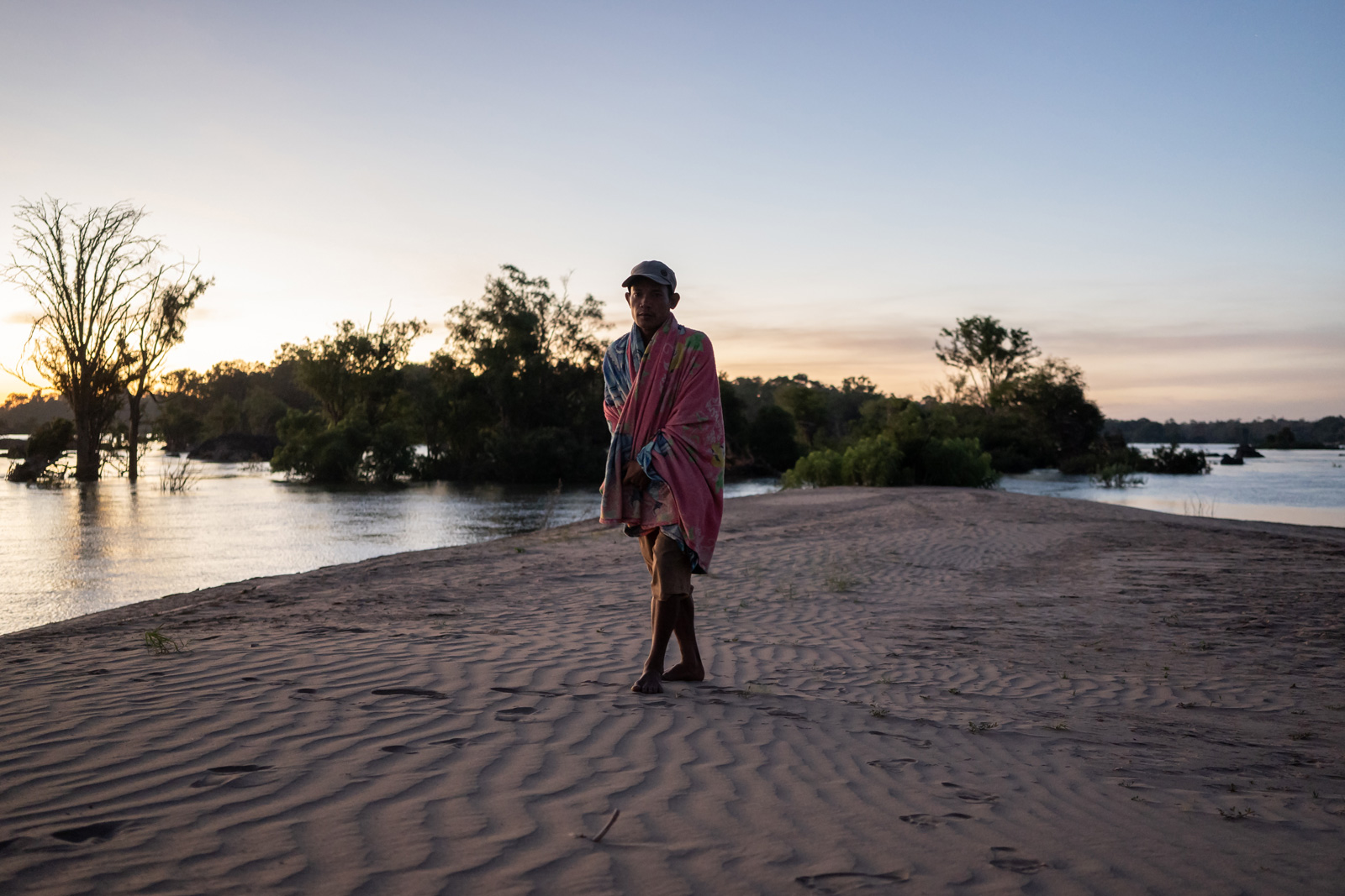A community fishery patroller wakes up on a sandbank in the Mekong River that the team had been camping on while on the lookout for illegal fishers.